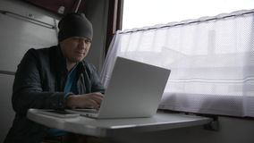 Young man on the train with his laptop stock footage