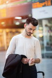 Young man at a train station. Attractive casual young man adjusting his smartwatch at a train station lobby; travel concept Stock Photo