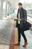 Young man at train station. Outdoor portrait of young handsome man standing at train station holding map in hands wearing warm coat Stock Photos