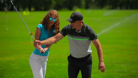 Young man train woman how to hit ball in golf stock footage