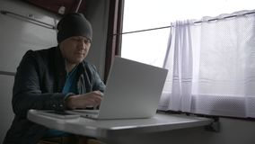 Young man on the train working on laptop stock footage