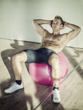 Young man training abs on fitness ball Royalty Free Stock Images