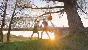 Young man training with a coach,boxing pad,sunset stock footage