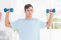Young man training with dumbbells Stock Image