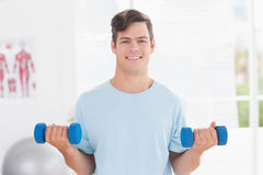 Young man training with dumbbells Royalty Free Stock Photography