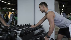 Young man is training with dumbbells sports club indoors. Promising bodybuilder is in intensive workout with free weight in modern gym. Handsome guy in gray t stock video footage