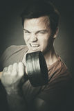 Young man training with dumbell Stock Photography