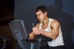 Young  man training on exercise bike Stock Photo