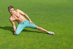 Young man training on green grass. Fit young man training outdoors on green grass royalty free stock photo