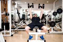 Young man training at gym with dumbbel Stock Image
