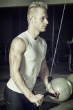 Young man training on gym equipment Royalty Free Stock Photography