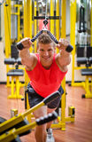Young man training on gym equipment Royalty Free Stock Photos