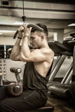 Young man training on gym equipment Royalty Free Stock Photo