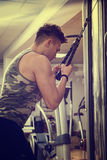 Young man training on gym equipment Stock Image