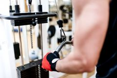 Young man training at gym with triceps exercises Royalty Free Stock Image