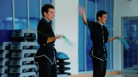 Young man training his skills in moving the sword in the gym stock footage