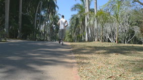 Young man is training outdoor. Male feet is running in the park trail. Legs of guy jogging. Slow motion stock video footage
