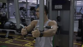 Young man is training in Pec Deck machine in gym indoors. Handsome guy spreads hands to sides, using iron equipment. Person is on intensive workout in modern stock video footage