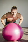 Young man training pecs on fitness ball Royalty Free Stock Photography