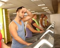 Young man training in running machine Stock Images