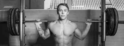 Young man training in smith machine Royalty Free Stock Images