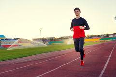 Young man is training at a sports stadium Stock Photos