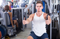 Young man training upper body using fly machine. Young men training upper body using fly machine in gym Royalty Free Stock Photos