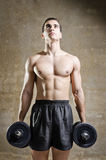 Young man training weights in old gym Royalty Free Stock Photography