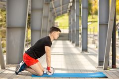 Young man training yoga outdoors. Sporty guy makes stretching exercise on a blue yoga mat, on the sports ground. Young man training yoga outdoors. Sporty guy royalty free stock image