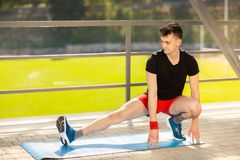 Young man training yoga outdoors. Sporty guy makes stretching exercise on a blue yoga mat, on the sports ground. Young man training yoga outdoors. Sporty guy stock photos
