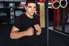 A young man trains in the gym, shakes on the gym triceps and bic royalty free stock photo