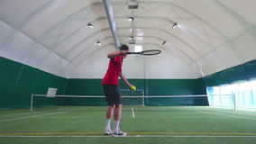 Young man trains on a tennis court forehand