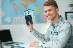 Young male travel agent consultant in tour agency holding documents. Young man travel agent in tour agency sitting holding passports and tickets smiling looking Stock Photography