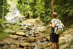 Young man with a travel backpack near a waterfall in Thailand Stock Photography
