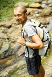 Young man with a travel backpack near a waterfall in Thailand Stock Images