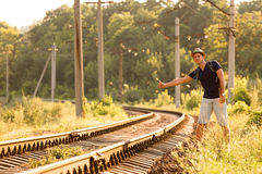 Young Man in Travel Clothing hitch hiking Railroad Train Royalty Free Stock Photography