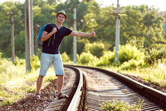 Young Man in Travel Clothing hitch hiking rural Railroad Train Royalty Free Stock Photo