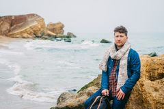 Young man traveler with a backpack standing on a rock against a beautiful sea with waves, a stylish hipster boy posing stock photography