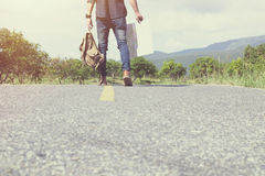 Young Man Traveler with backpack walking on the road outdoor. Summer vacations and Lifestyle hiking concept Royalty Free Stock Photo