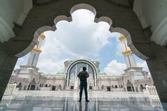 Young man traveler with backpack walking to Wilayah Persekutuan. Mosque in Kuala Lumpur, Malaysia Stock Image