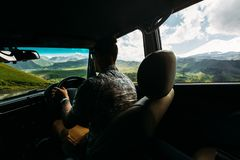 Young Man Traveler Driving A Car In The Mountains In Summer, Rear View From The Car. Young man autotravel manages a car against a backdrop of a picturesque royalty free stock image