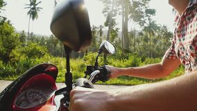 Young man traveler driving motorbike on tropical sunny road through the sun with beautiful lens flare effects in a. Young man traveler driving motorbike on stock video