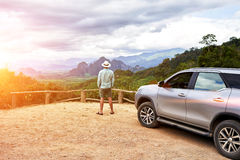 Young man traveler is enjoying gorgeous view during his road trip on suv in Thailand Royalty Free Stock Photo