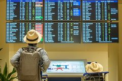 Young man traveler with hat checking flight time, Asian passenger looking to information board in international airport terminal. royalty free stock photo