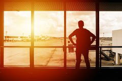 Young man traveler looking outside of terminal window at airport. Silhouette of young man traveler looking outside of terminal window at airport before departure Stock Images