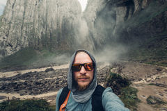 Young Man Traveler Makes Selfie On  Background Of Waterfall And Mountains In Summer Stock Photos