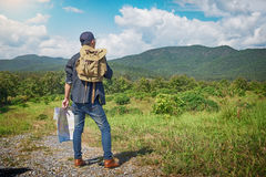 Young Man Traveler with map backpack relaxing outdoor with rocky Stock Photography