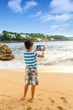 The young man  traveler photographing sea island view Royalty Free Stock Images
