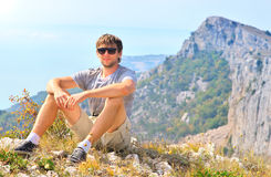 Young Man Traveler relaxing with Mountains on background Royalty Free Stock Images