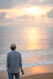 Young man traveler seeing sunset at tropical beach Royalty Free Stock Image
